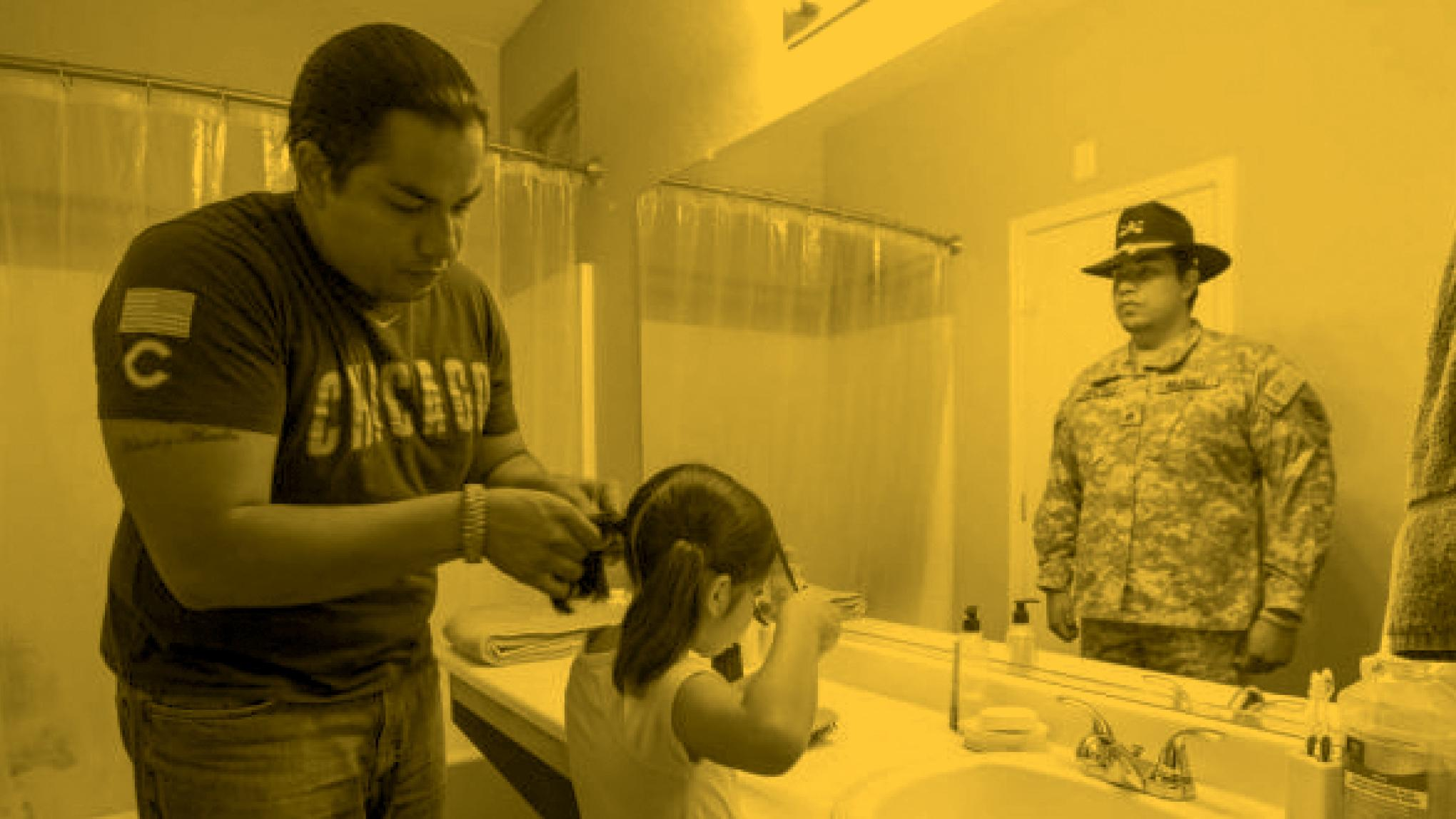 Photo of G. Vergara Calderon braiding child's hair, photo by Devin Mitchell, Veteran Vision Project